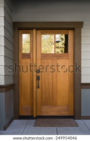 Natural Wood Front Door on Grey and Blue Siding Exterior with Large Slate Tiles and Doormat