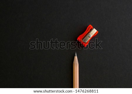 Natural wood pencil on the black surface with red color sharpener.Space for text,conceptual image of education.