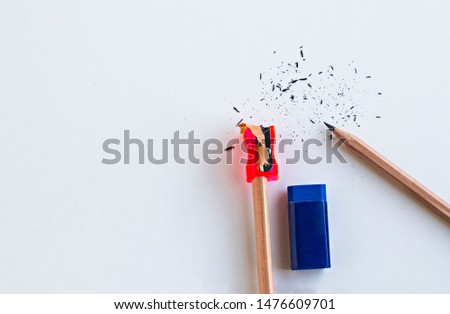 Natural wood pencils with red sharpener and blue rubber on the white surface.Conceptual image of education.