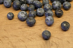 Natural wooden background. Food background. Blueberries ripe and tasty on a wooden table. A large plan, a top view, rustic style.
