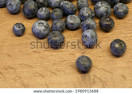 Natural wooden background. Food background. Blueberries ripe and tasty on a wooden table. A large plan, a top view, rustic style. Photo stock ©