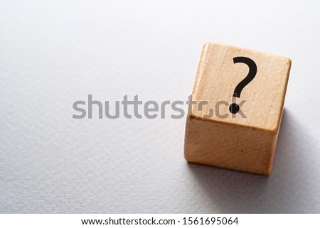 Natural wooden cube or dice with question mark