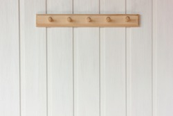 natural wooden empty hanger on a white wall. rustic interior as background, copy space.