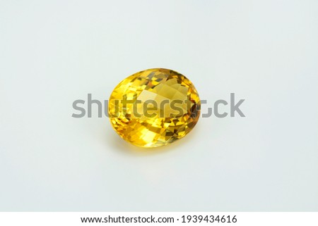 Natural yellow brazilian citrine quartz oval checker faceted gemstone. Unheated, clean, transparent, sparkling, shiny on white backgound. Semiprecious gemstone setting for big solitaire rings.