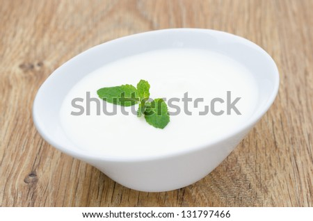 natural yogurt with mint leaf on a wooden table