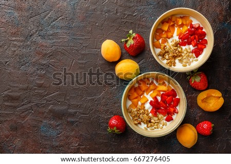 Natural yogurt with pieces of apricots, strawberries, granola and pine nuts in two bowls on dark broun background. Top view with place for text #667276405