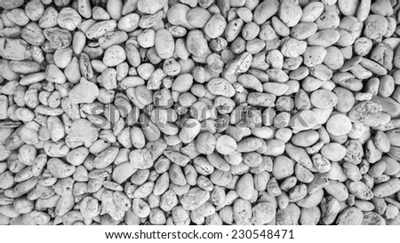 Naturally polished white rock pebbles background, black and white