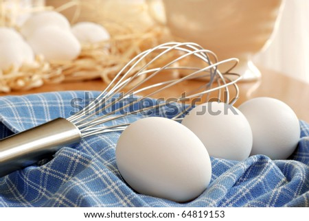 Naturally sunlit still life of fresh eggs with whisk on kitchen table.  Eggs with raffia in background.  Closeup with shallow dof.