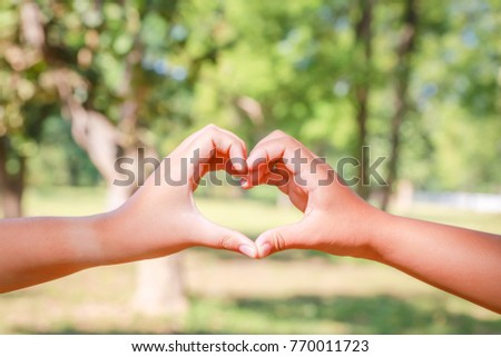 Nature background concept: Heart-shaped hands naturally blur the background. #770011723