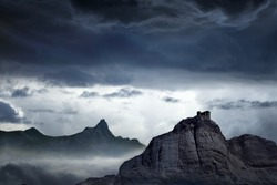 Nature background - dark stormy sky above mountains, fortress on top of rock