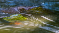 Nature background of a wild stream detail flowing over mossy stones. Abstract green and blue dynamic wavy water surface with motion blur on white streamlines. Close-up of fast running swift creek bed.