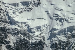 Nature background of big rocky snowy mountain wall with white glacier and snow cornice close up. Beautiful natural texture of sunlit snowy mountainside. Full frame of black white high mountains.