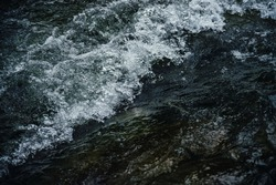 Nature background of dark water stream of mountain river with rapids. Full frame of sea surf. Natural textured backdrop of ocean surf. Texture of tide close-up. Dark water surface of mountain creek.