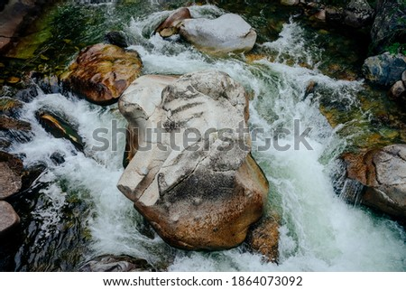 Photo of  Nature background with cascades of mountain creek close-up. Scenic landscape with beautiful mountain brook with green water. Idyllic scenery with green water in small river. Fast water flow closeup.