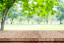 Nature background, Wood table for food and product display over blur green tree garden, Blur park nature outdoor and wood table with bokeh light background in spring and summer