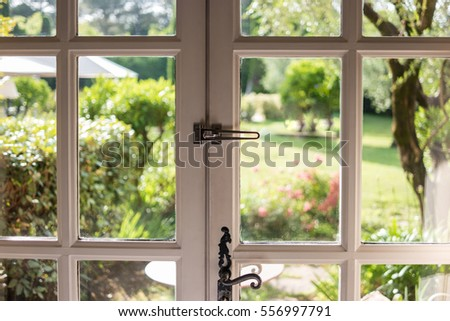 Nature behind door. White frame and dark handle. Look through the glass.