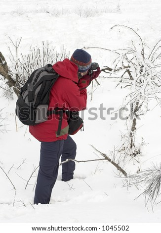 Nature female photographer staying in the snow and making a photograph.