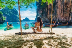 Nature for life, Healthy woman in bikini relaxing on swing practicing yoga pose on destination natural island, Krabi, Wellness girl traveling tropical sea beach Thailand, Summer vacation travel trip