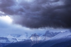 Nature force background - dark stormy sky in snowy mountains
