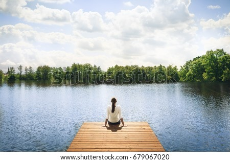 Nature getaway.  Woman sitting on a wooden dock next to lake.