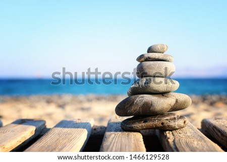 nature image of stones pyramid on over beach wooden deck symbolizing harmony, zen and balance