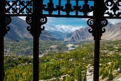 Nature landscape lush green forest of Hunza Nagar valley view from Baltit fort. A view of winding river flowing along the valley and  Rakaposhi mountain in Karakoram range. Gilgit Baltistan, Pakistan.