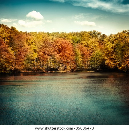 Nature landscape with beautiful lake in autumn with colorful trees and blue sky with cloudscape in the background.