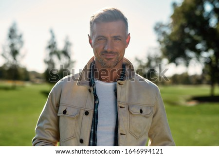Nature making us happy. Portrait of handsome and stylish bearded man looking at camera and smiling while standing in the middle of the park. Nature concept. Beautiful people