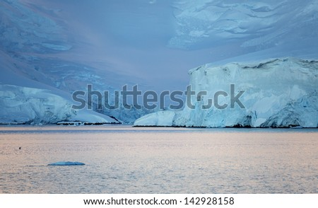 Nature of Antarctic Peninsula. Early morning in the Antarctic fjords. Glaciers and icebergs. Travel on deep pure waters among ices of Antarctica. Fantastic snow landscapes.