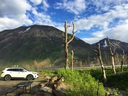 Nature photo of two mountains with patches of snow on sunny day, white clouds on bright blue sky, white car on rest area parking next to burned trees with no leaves, green grass, road stop, June 2020
