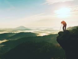 Nature photographer in the action.  Man silhouette above a misty clouds,  morning hilly landscape.