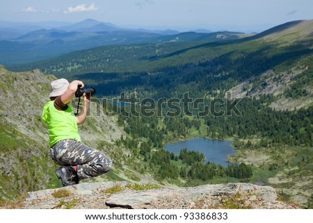 Nature photographer taking pictures outdoors during hiking trip on Altai mountains, Siberia