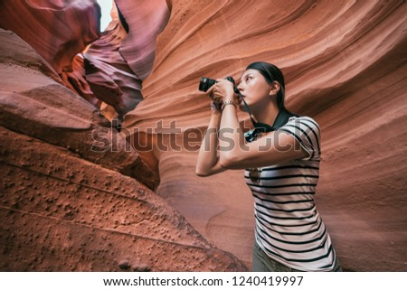 Nature Photographer taking pictures outdoors lower antelope canyon arizona. young lady lens man concentrated holding camera zoom up. beautiful woman self guided travel in america.