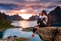 Nature photographer tourist with camera shoots while standing on top of the mountain. Beautiful Nature Norway Lofoten archipelago.