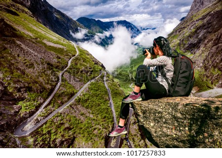 Nature photographer tourist with camera shoots while standing on top of the mountain. Troll's Path Trollstigen or Trollstigveien winding mountain road in Norway.