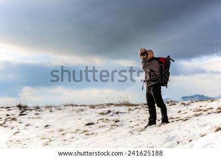 Nature photographer trekking in the mountains winter - Shutterstock ID 241625188