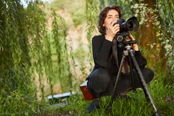 Nature photographer with camera and tripod in landscape photography as a hobby
