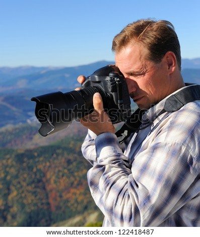 Nature photographer with digital camera on top of the mountain