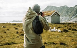 Nature photographer works. Photographer working, look to Norwegian landscape with typical scandinavian grass roof houses and the sheep grazing in the valley