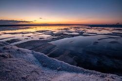 Nature reserve Saline Margherita di Savoia, Apulia, Italy: Salt flats area for sea salt production. marsh, an ecosystem on Adriatic sea. Heaps of salt at sunset ready for harvest