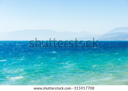 Stock Photo Nature seascape background: blue and turquoise sea with mountains and sky over it.