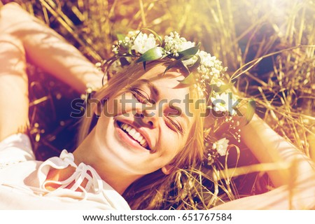 nature, summer holidays, vacation and people concept - happy smiling woman in wreath of flowers lying on straw