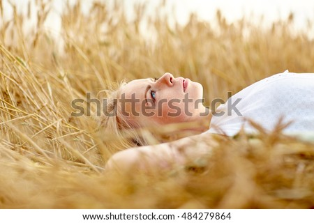 nature, summer holidays, vacation and people concept - young woman or teenage girl lying and dreaming on cereal field #484279864