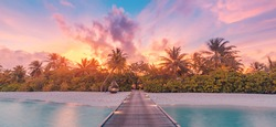 Nature sunset on Maldives island, luxury water villas resort and wooden pier. Beautiful sky clouds and beach nature background for summer vacation holiday and travel concept. Paradise sunset landscape