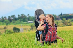 Nature walk in green rice terrace field. Happy mother hold little traveller in carrying backpack. Baby ride on woman back. Travel adventure, hiking with child carrier, family summer vacation on Bali.