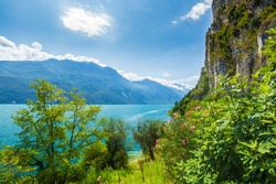 Nature wilderness landscape at lake Garda, Italy on a beautiful summer day. Blue water, rocks, mountains, sunlight and clear sky.
