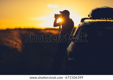 Nature Wildlife Photographer Working in the Field. Senior Photographer Taking Pictures on the Country Road While Supporting His Back on His Vehicle. Scenic Countryside Sunset.