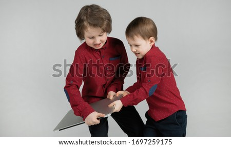 Naughty and active boys in isolation during quarantine. Two emotional brothers are trying to steal a laptop from each other for watching cartoons. Children are bored while at home. Cronovirus