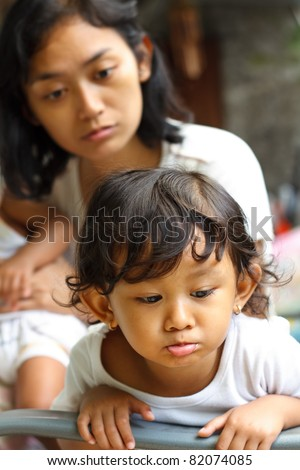naughty asian ethnic little girl being advised by mom