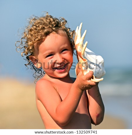 Naughty blond boy on the coast of the Black Sea - stock photo